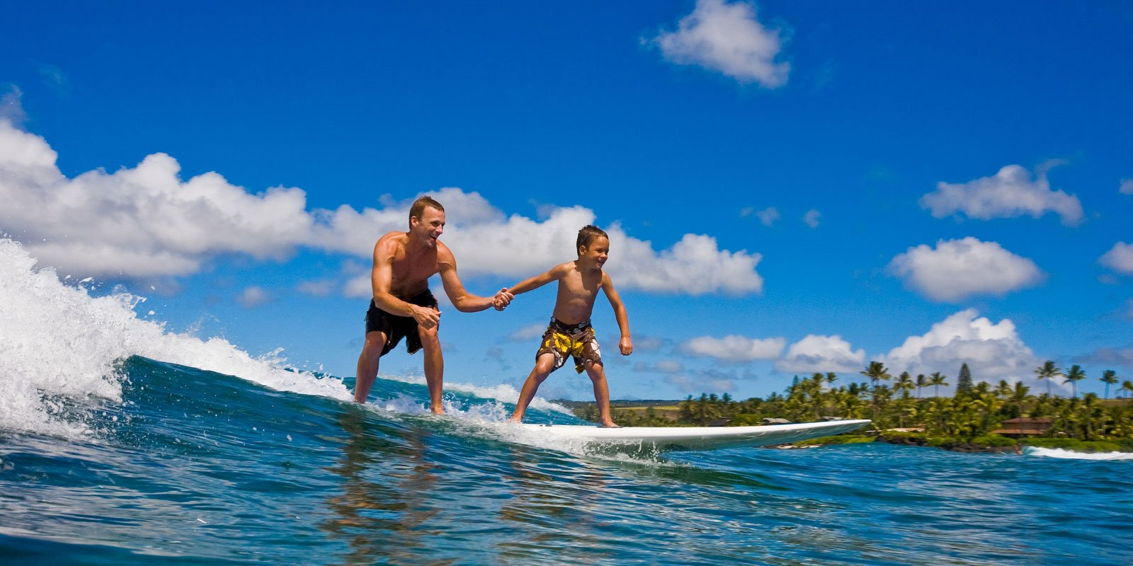 father and son surfing poipu